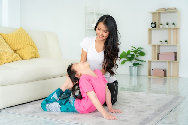 Asian mother and daughter doing yoga exercises in living room at home