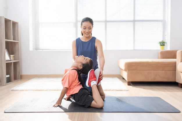 Asian mother and daughter exercising at home they are doing yoga