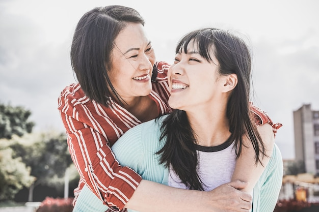Asian mother and daughter having fun outdoor - happy family people enjoying time together around city in asia