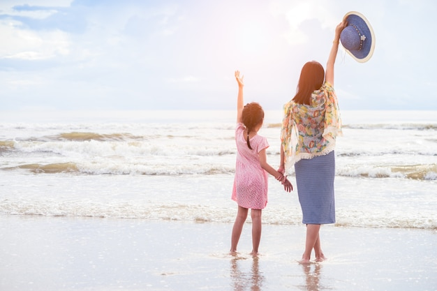 Asian mother and daughter hold one's hands on the beach