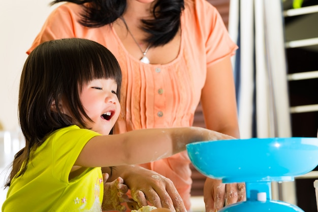 Asian mother and daughter at home in kitchen