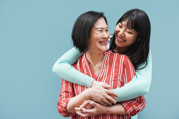 Asian mother and daughter hugging outdoors with blue