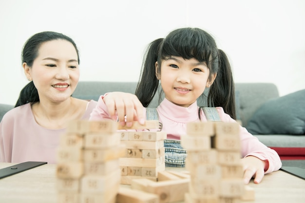 Asian mother and daughter playing wood block tower stacking game in cozy modern home