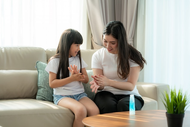 Asian mother and daughter using wash hand sanitizer gel bottle dispenser