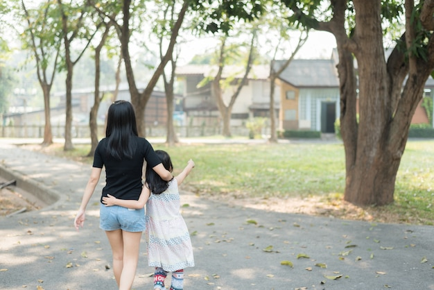 Asian mother and daughter walking together in a warm embrace. represents a good rapport within the family, happy family time