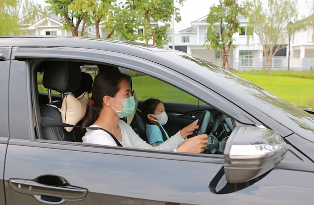 Asian mother and daughter wears hygiene face mask sit in car during coronavirus (covid-19) outbreak