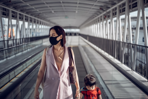 Asian mother and daughter with medical mask on the city street. life during covid-19 pandemic.