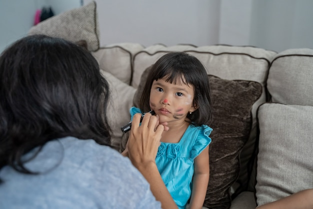 Asian mother face painting her little daughter