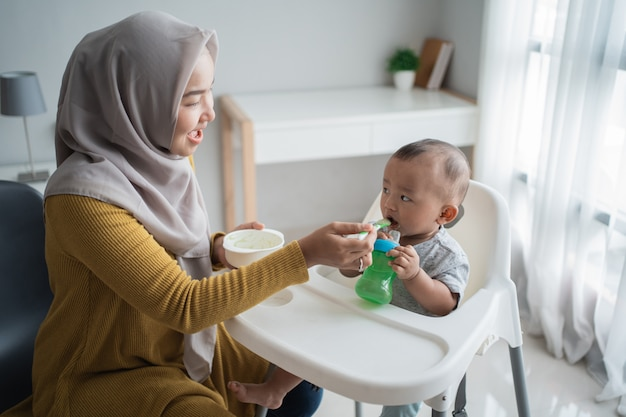 Asian mother feeding her baby son with spoon