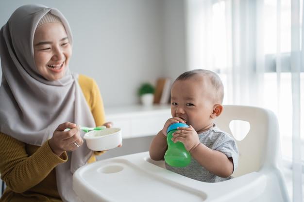 숟가락으로 그녀의 아기 아들을 먹이 아시아 어머니