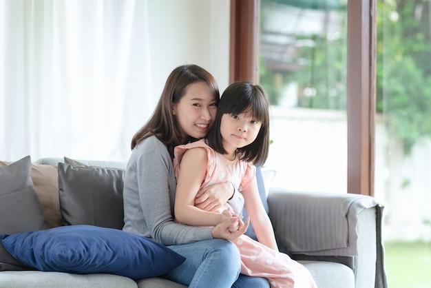 아시아 어머니는 집에서 사랑과 보살핌으로 귀여운 딸을 안아주는 동안 행복을 느낀다