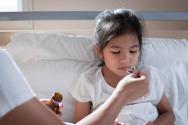 ベッドで娘にスプーンで咳止めシロップ薬を与えるアジアの母親