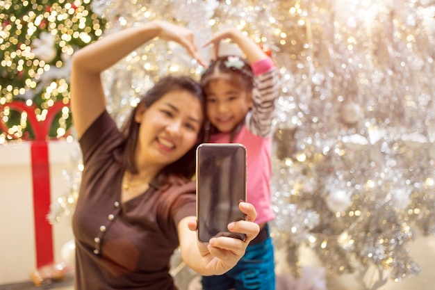 Asian mother hand hold mobile with daughter to take selfie photo