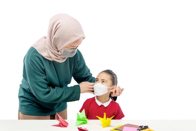 아시아 어머니 손 흰색 배경에 고립 된 그녀의 딸에 마스크를 씌우고