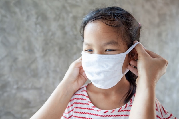 Asian mother help her daughter wearing protection mask to protect the coronavirus covid-19 outbreak situation and air smog pollution with pm 2.5