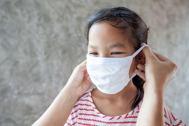 Азиатская мать помогает своей дочери носить защитную маску для защиты от вспышки коронавируса covid-19 и загрязнения воздуха смогом с pm 2.5