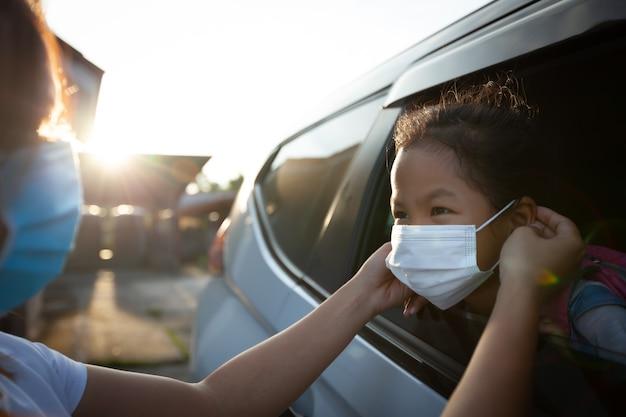 アジア人の母親は、学校に行く前に、保護マスクを着用してコロナウイルスcovid-19の発生状況を保護するために娘を助けます。学校のコンセプトの準備をしなさい。