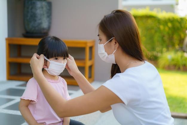 Азиатская мать помогает дочери носить защитную маску