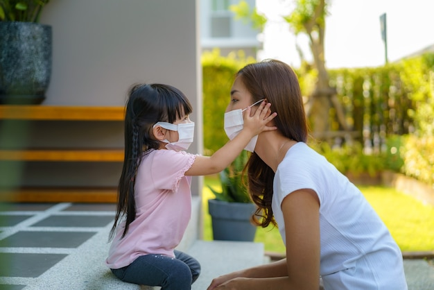 Asian mother help her daughter wearing protection mask