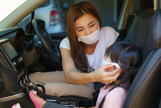 アジアの母親は、保護マスクを身に着けている娘を助けます