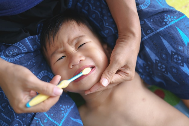 Asian mother helping her boy brushing teeth for dental care