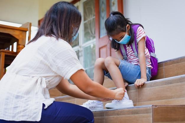 アジアの母親は、コロナウイルスcovid-19のパンデミックの際に、娘が靴紐を結び、保護フェイスマスクを着用して外出するのを手伝っています。