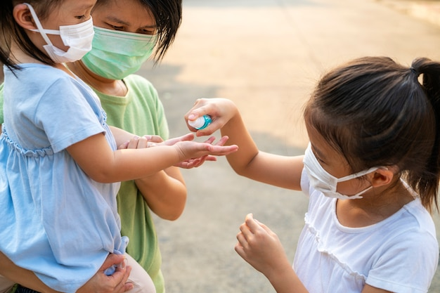 Asian mother helping her daughter wearing protective mask for protection corona virus or covid 19 virus outbreak