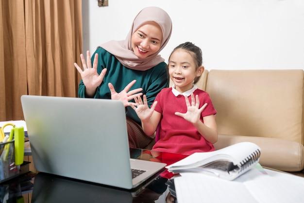 アジアの母親は、自宅でラップトップを使って宿題をしている少女を助けています。検疫中のオンライン教育