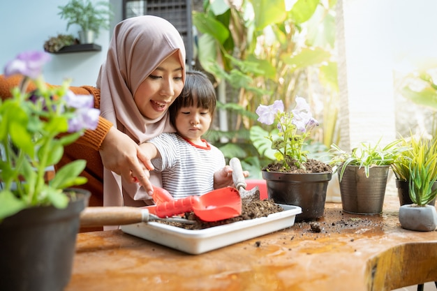Asian mother helps her daughter take soil with a small shovel from a tray for planting media