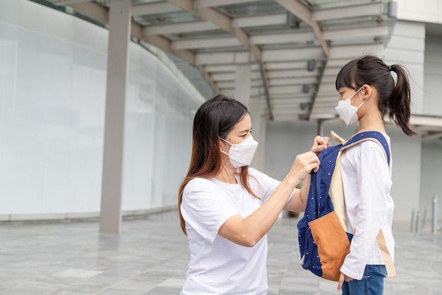 アジア人の母親は、保護のために医療用マスクを着用している娘がcovid-19またはコロナウイルスの発生により、学校の命令に戻ったときに学校に行く準備をするのを手伝っています。