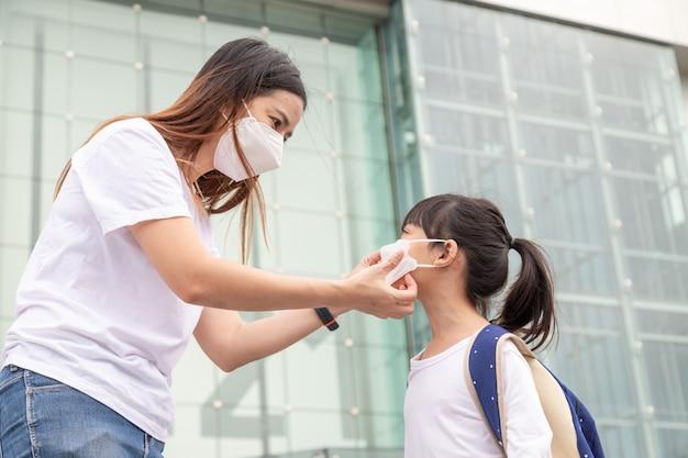 アジアの母親は、娘がcovid19またはコロナウイルスを保護するための医療用マスクを着用するのを手伝っています