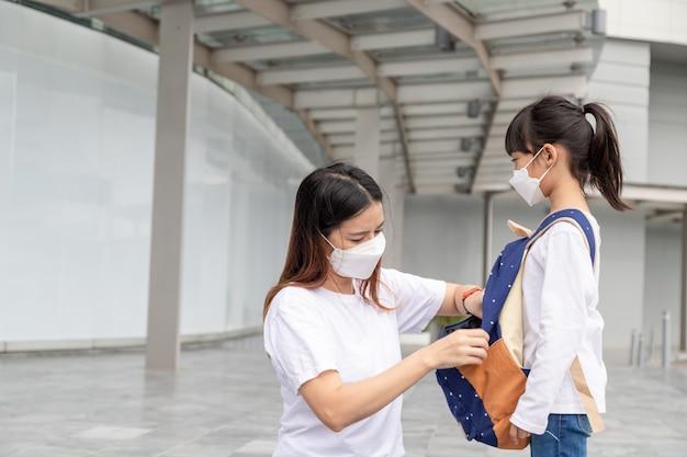 アジアの母親は、娘が保護のために医療用マスクを着用するのを手伝っていますcovid19の発生