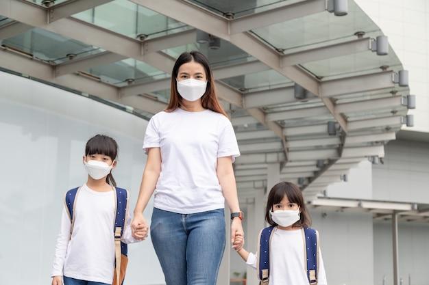 아시아인 어머니는 코비드19 발병을 보호하기 위해 의료용 마스크를 쓴 딸을 돕습니다.