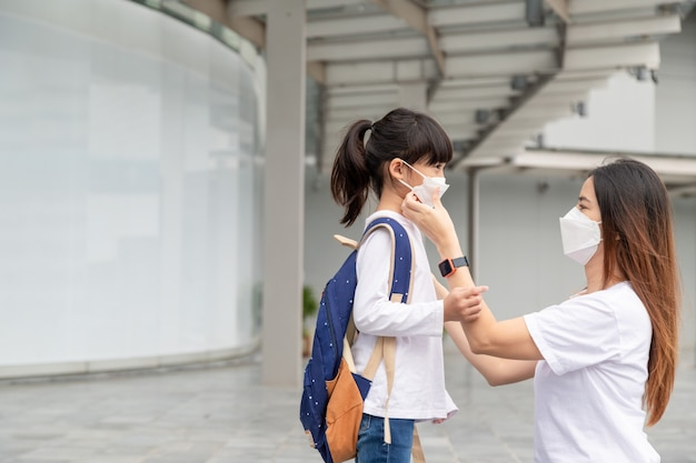 Asian mother helps her daughter wearing a medical mask for protection covid-19 or coronavirus outbreak prepare to go to school when back to school order.