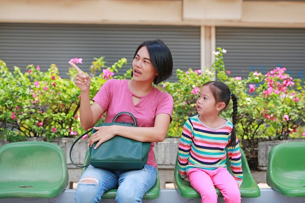 Asian mother and her daughter sitting at bus station