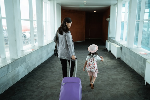 An asian mother and her daughter walked up and pulled a suitcase