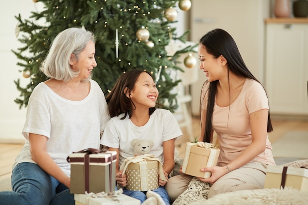 Asian mother and her daughter with granddaughter congratulating each other with christmas and giving presents sitting on the floor