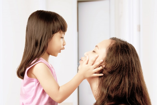 Asian mother and her little girl playing together