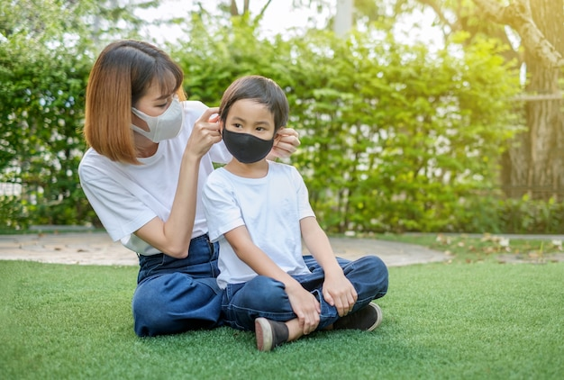 Asian mother and her son wearing protective masks