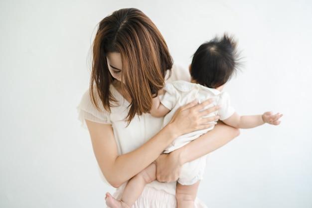 赤ちゃんを抱いて疲れているアジアの母親