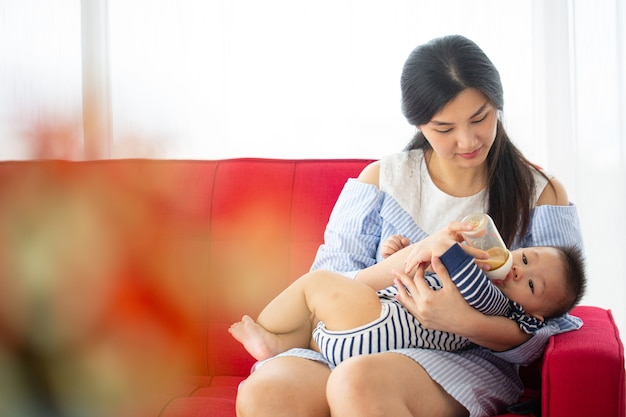 Asian mother holding her baby beside bedroom.