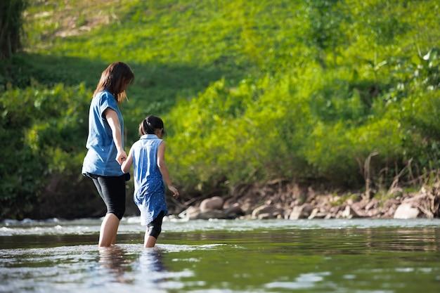Азиатская мать держит ребенка за руку, чтобы вместе гулять и играть в реке