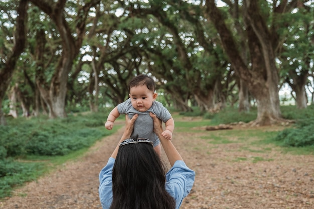 Asian mother holding up a baby in the park