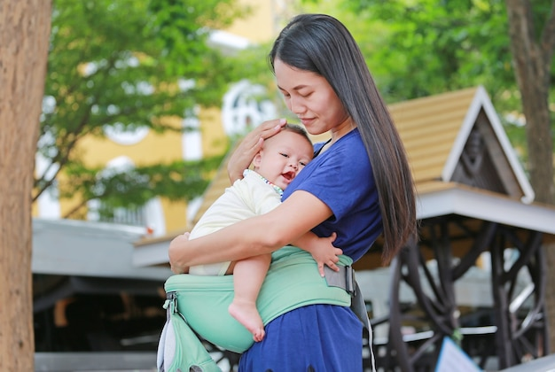 Asian mother hugging her infant on ergonomic baby carrier.