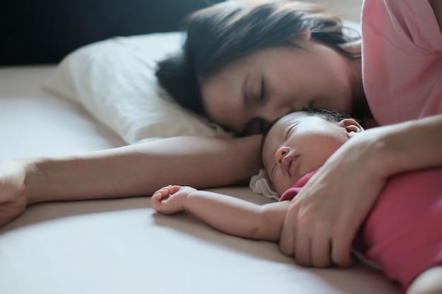 アジアの母親がベッドで寝ている彼女の生まれたばかりの赤ちゃんを抱き締めます。