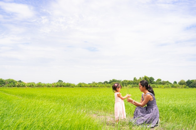 Asian mother is giving the flowering grass to her daughter in background of rice field.