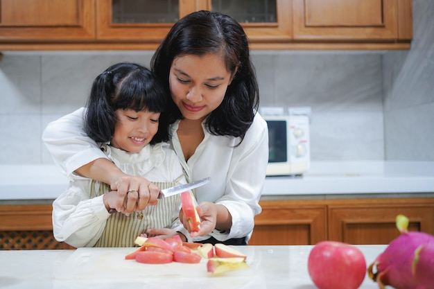 Asian mother is teaching her little daughter cutting apple in the kitchen at home.
