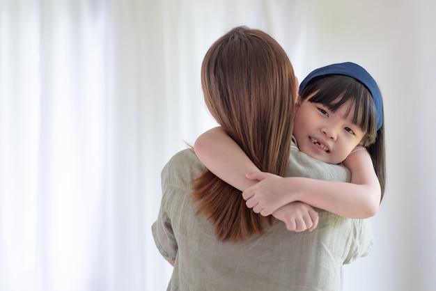 Азиатская мать занимается любовью с теплыми объятиями своей милой дочери дома
