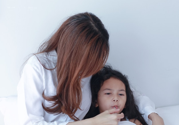 Asian mother measuring temperature of her daughter