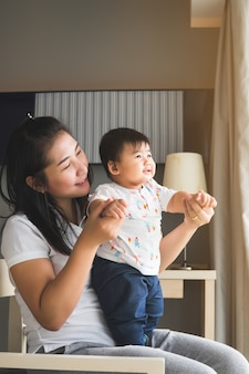 Asian mother playing with her baby in the bedroom.